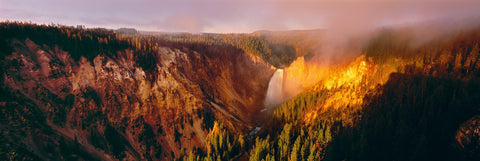 Sunlight hitting the mist covered waterfall and mountainside of Artist Point Yellowstone National Park Wyoming
