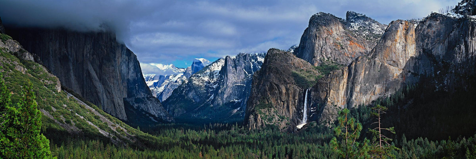 Yosemite Valley covered by clouds with the waterfall and snow covered mountains in the background