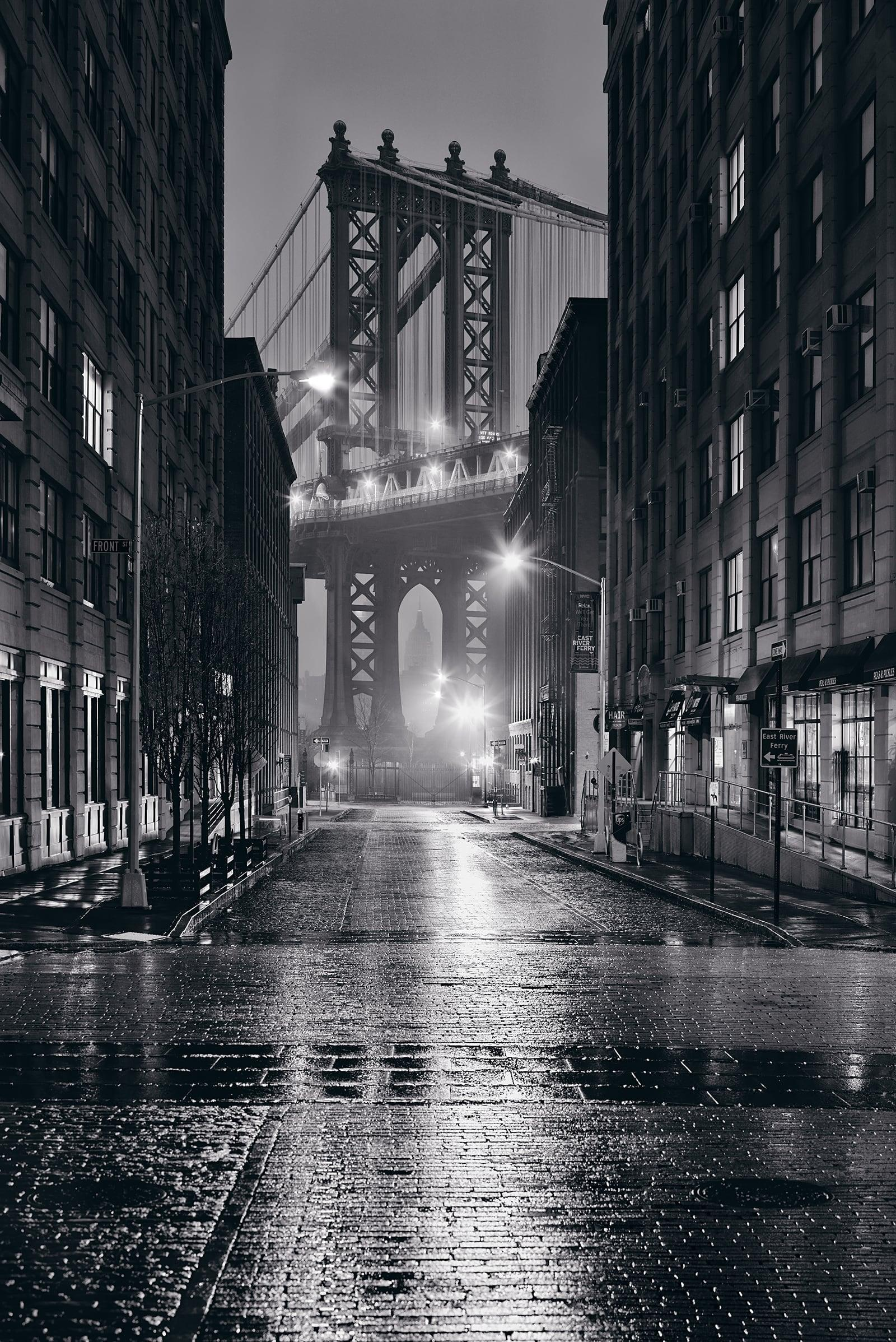 Black and white wet city street at night and the Manhattan Bridge in New York