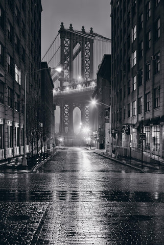 Black and white wet city street at night leading to the Manhattan Bridge in New York City