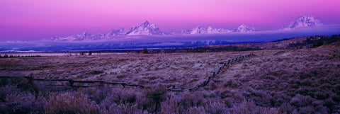 Wooden post fence running through a frost covered valley in front of the Grand Teton Mountains