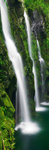 Three waterfalls of Wailele pouring down moss covered rock walls into a pool of water in Hana Hawaii