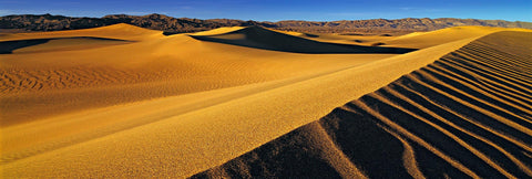 Yellow windswept sand dunes in front of the rock hills of Death Valley California