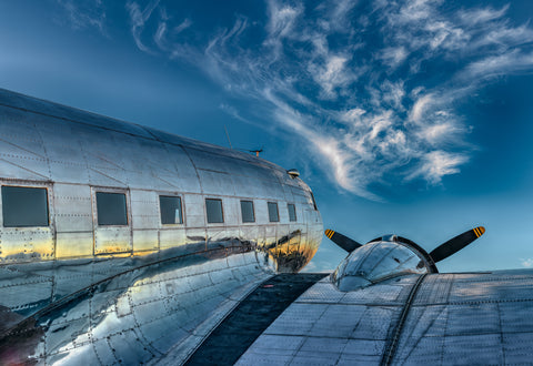 Back side view of a DC-3 airplane looking out to a blue sky and whispy clouds in Aurora Oregon
