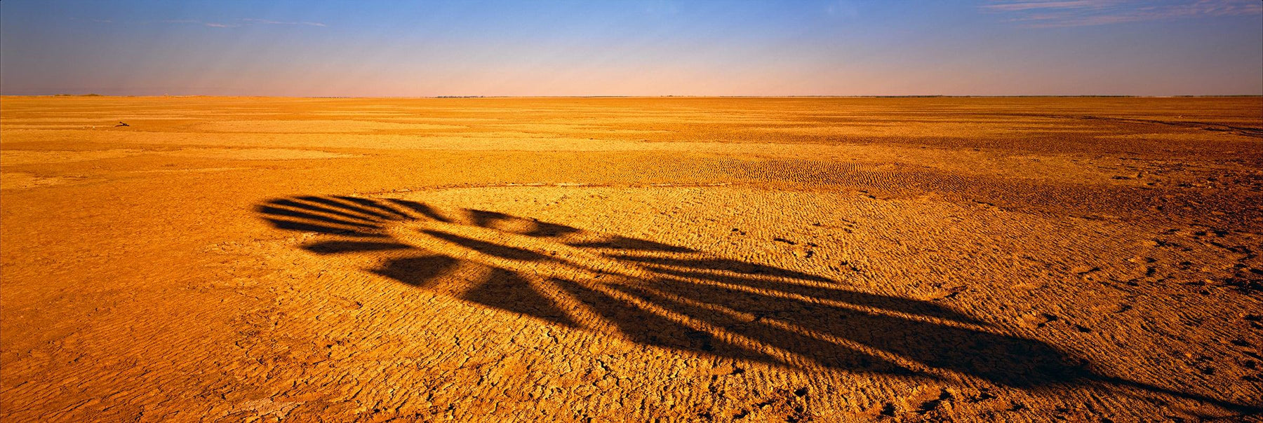 Shadow of a windmill blades being cast onto the dry desert floor in Normanton Australia