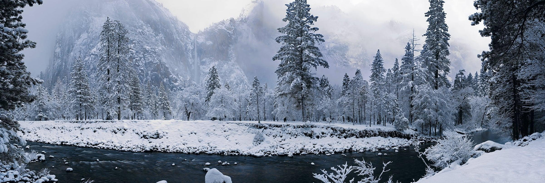 River running through the snow covered forest of Yosemite National Park California with a waterfall in the background
