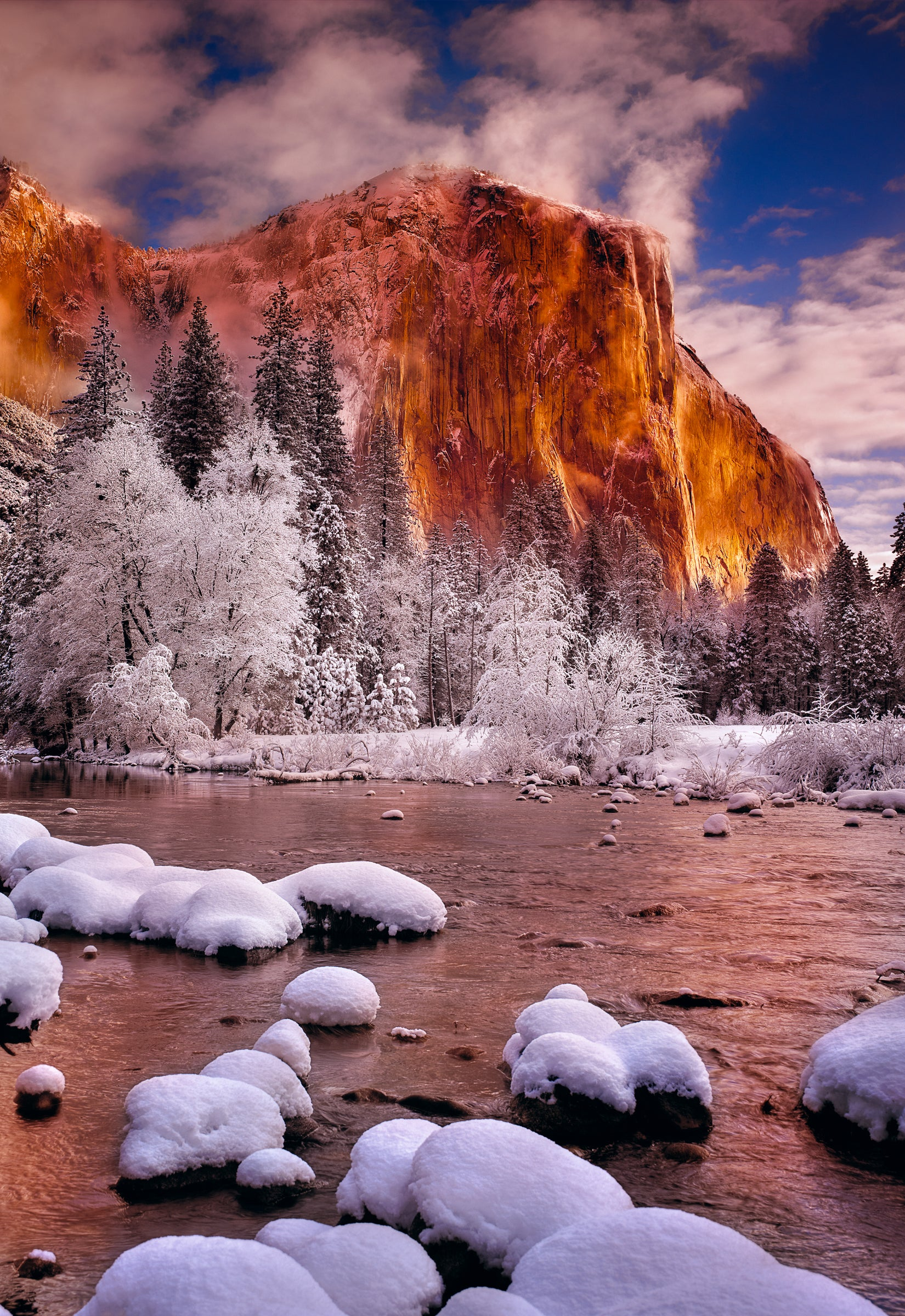 Snow covered rocks in a river running in front on El Capitan and through Yosemite National Park