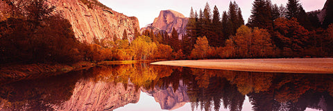 Reflection of Half Dome in a river running through Yosemite National Park with the surrounding colors of Autumn