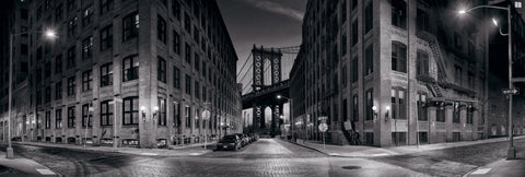 Black and white New York street with buildings leading to the Manhattan Bridge in the background at dusk