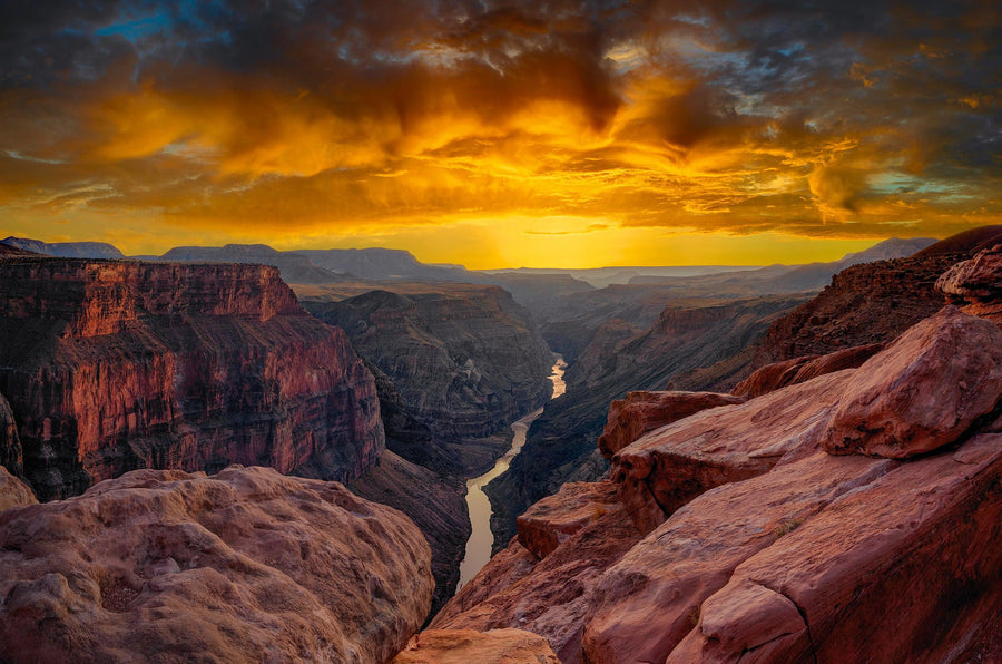 View from a rocky cliff of the Grand Canyon Arizona overlooking the Colorado River below at sunset
