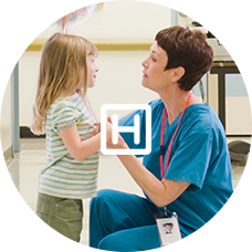 Female nurse kneeling down to talk to young girl patient