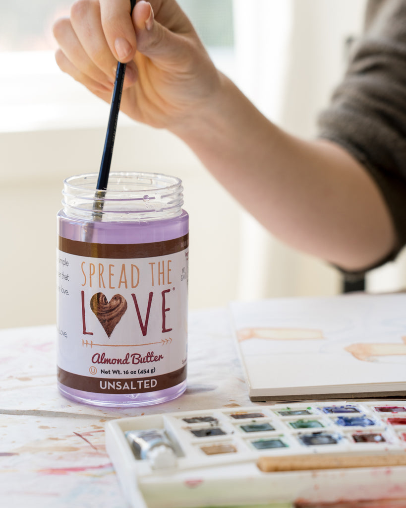 Spread The Love jar used to wash a paintbrush