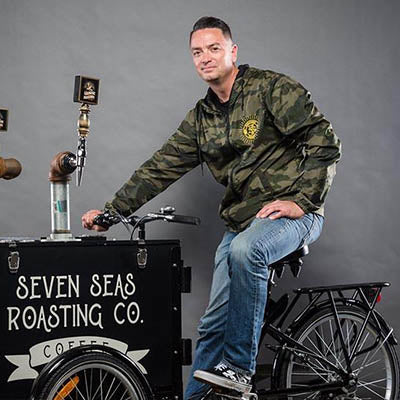 eric dobbs, caucasian male on cold brew bike wearing camo jacket and blue jeans