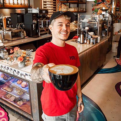 Josh Sitton, caucasian male smiling and showing us a latte in a specialty coffee cafe