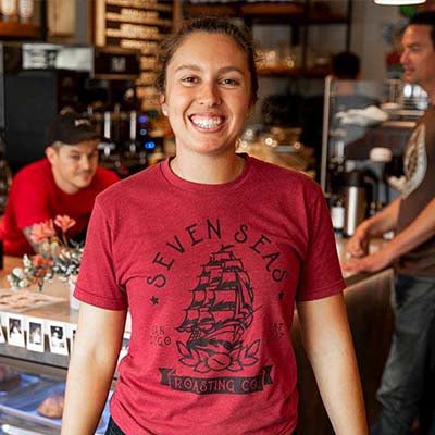 Liav Cloughley, Jewish female wearing red shirt smiling in seven seas roasting specialty coffee cafe.