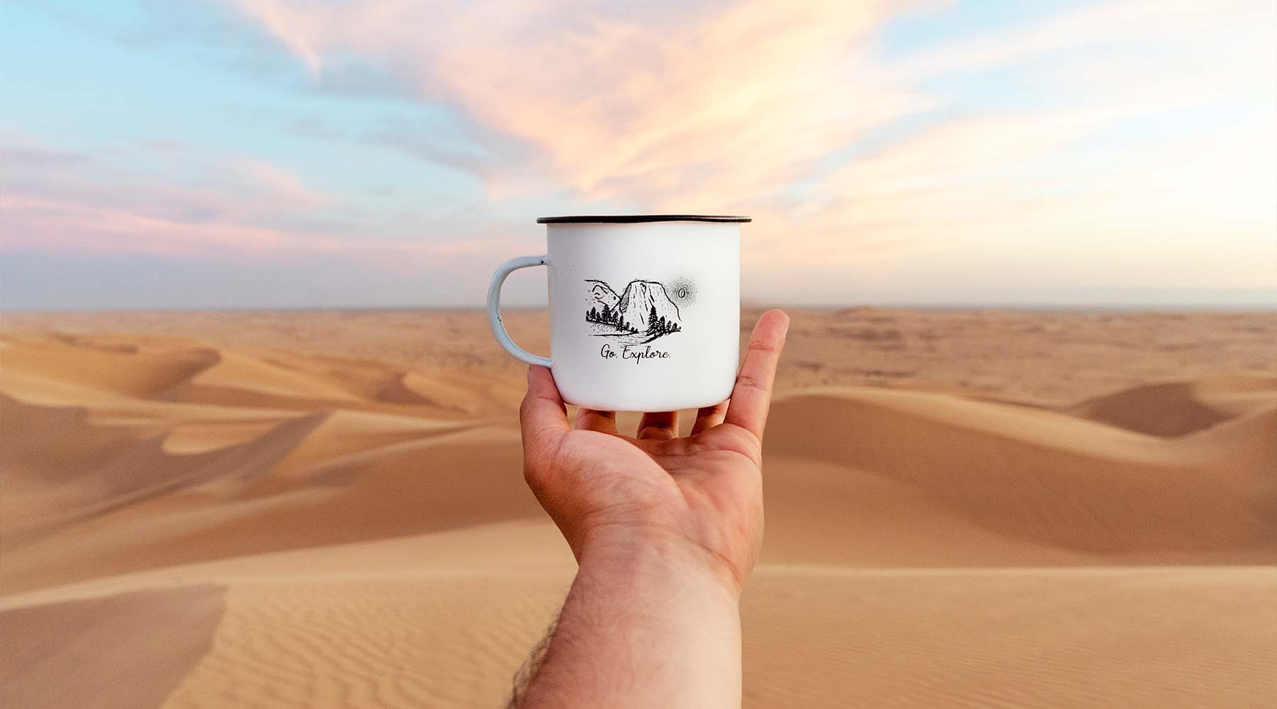 Glamis sand dunes desert with a seven seas roasting mug in the foreground with an hand holding it mid air.