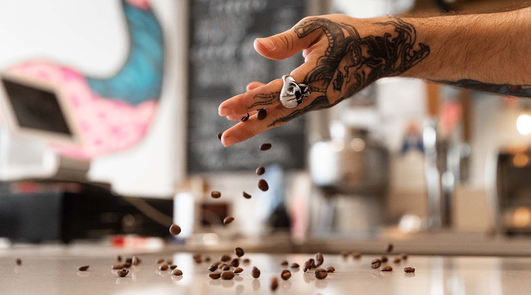 Hand in a cafe dropping coffee beans on to the cafes counter top