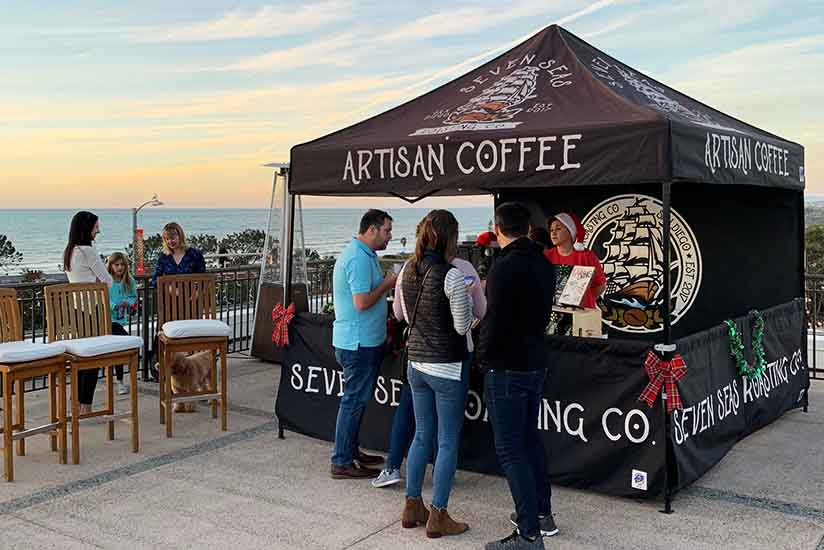 Seven Seas Roasting La Jolla farmers market tent during December markets. barista wearing Santa hat and three customers purchasing coffee.