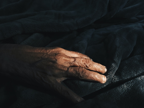 A bony and veiny hand lying on the blanket