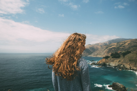 curly-haired girl on a cliff by the sea