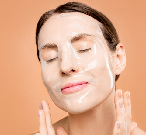 woman applying anti-aging cream to remove dark spots from face