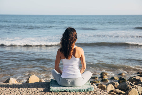 Woman in seated meditation on sage Ritual Rug looking at the ocean. Comfortable for any yoga or meditation practice, The Ritual Rug offers cushion and support.