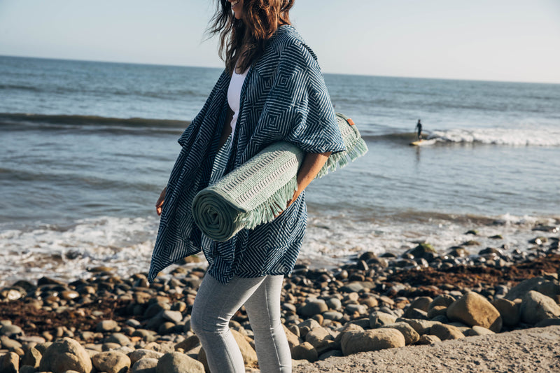 woman walking with sage handwoven yoga mat on beach