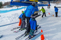A camp of skiers boards the lift with the help of an instructor