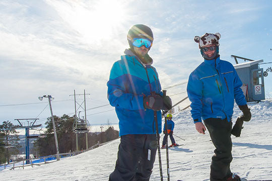 An instructor stands with another skier at the top of the hill