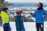 Instructor with two students smiling at the top of the hill