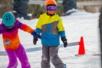 Two young snowboarders line up to ride the lift
