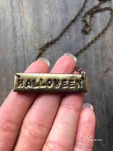 Hand stamped, gold coloured clay necklace with the text Halloween