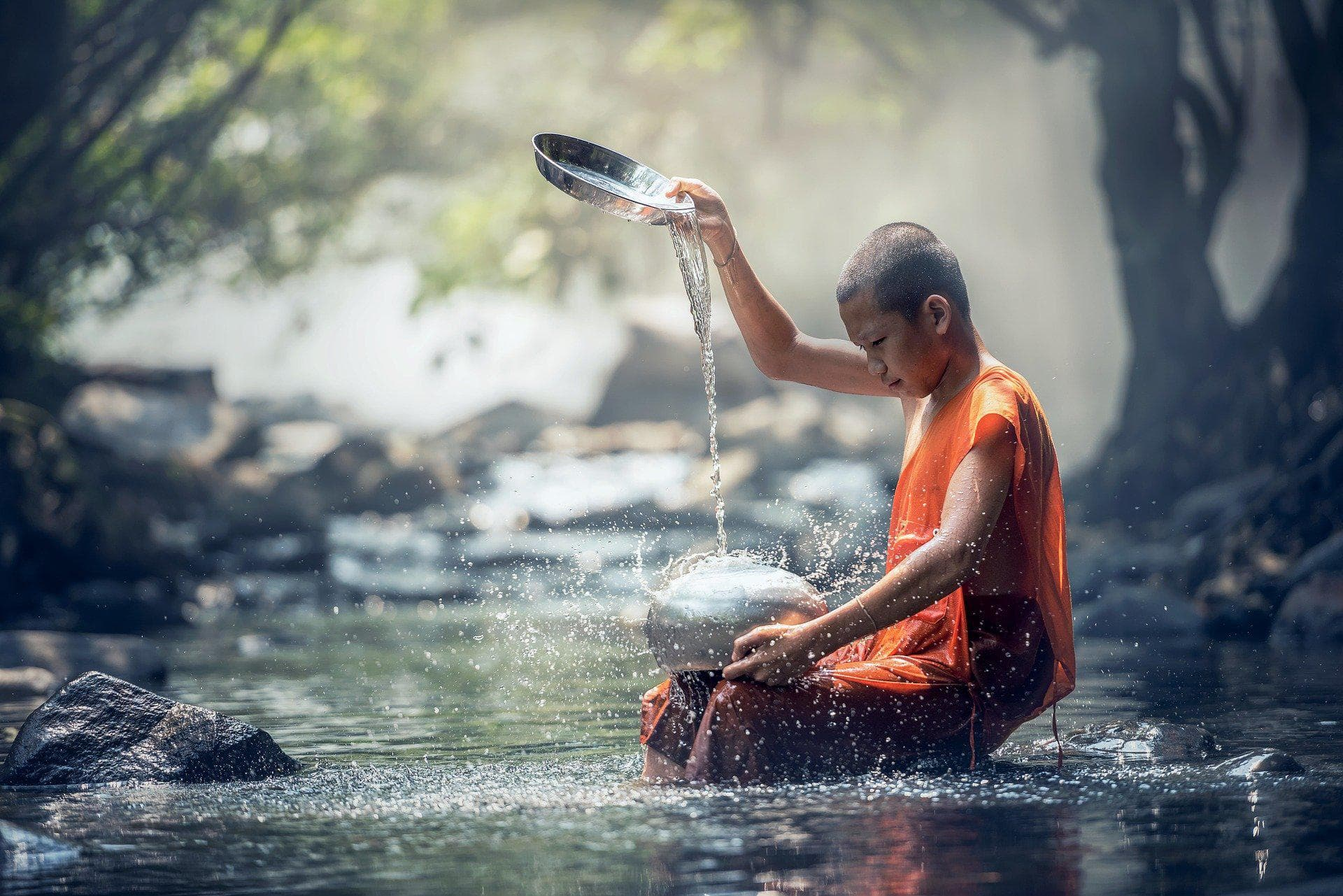 monk cleaning bowl at river