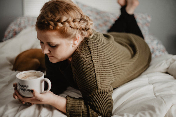 Girl drinking coffee in bed