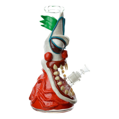 Sideview of 12 inch bong with shape and look of scary angry Giggles the Clown head many teeth facing right bowl on right