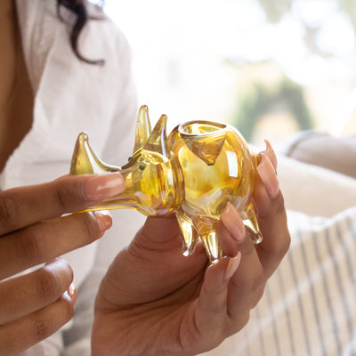 Woman with long peach colored nails holding a cute 2.6oz golden rhino shaped glass pipe smoking device