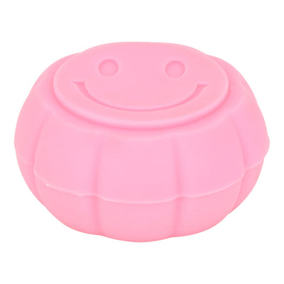High angle and front shot of pink round silicone container smoking accessory with smiley design on lid