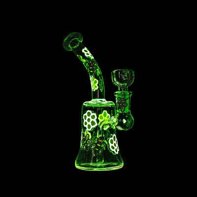 Full shot of glow in the dark 7 inch glass bong with honey bee and yellow flower petal designs in black background