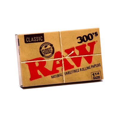 Full shot of tied and packaged in cardboard RAW 300s classic 1 1/4 rolling papers with big RAW word in red
