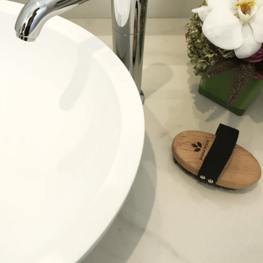 Prana Brush dry brush placed on a bathroom counter beside sink
