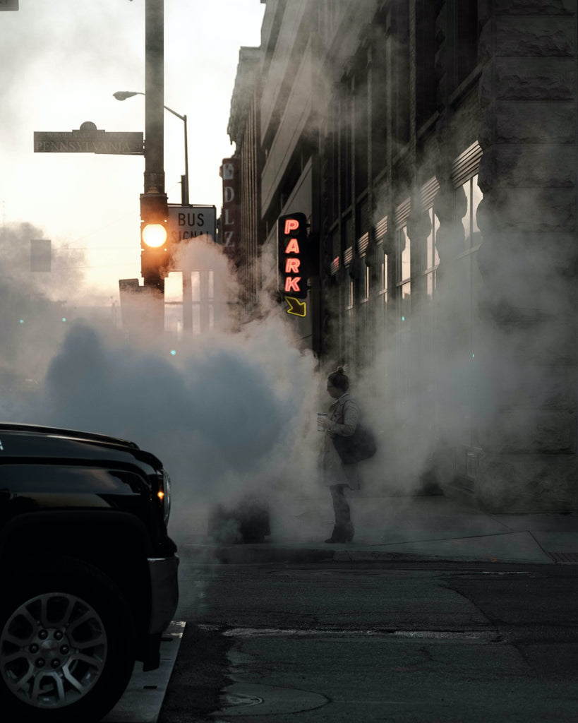 woman standing near buildings and car covered in smoke