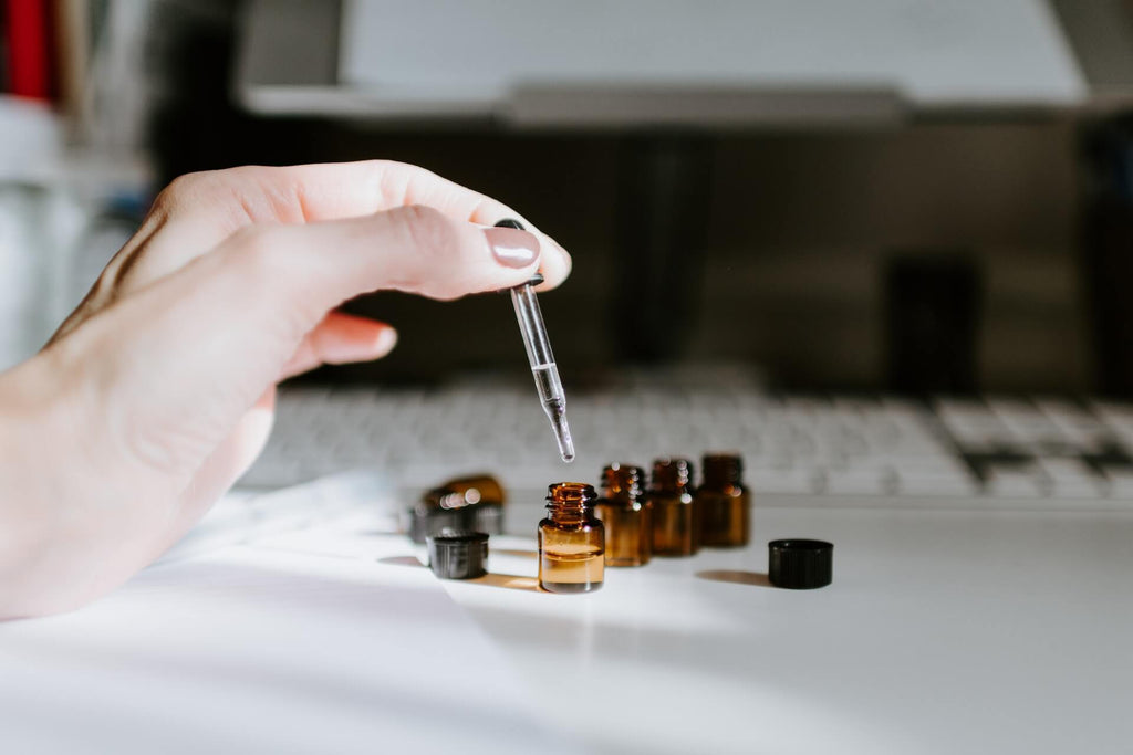 tiny brown bottles placed on white table while hand dropping essential oil inside one