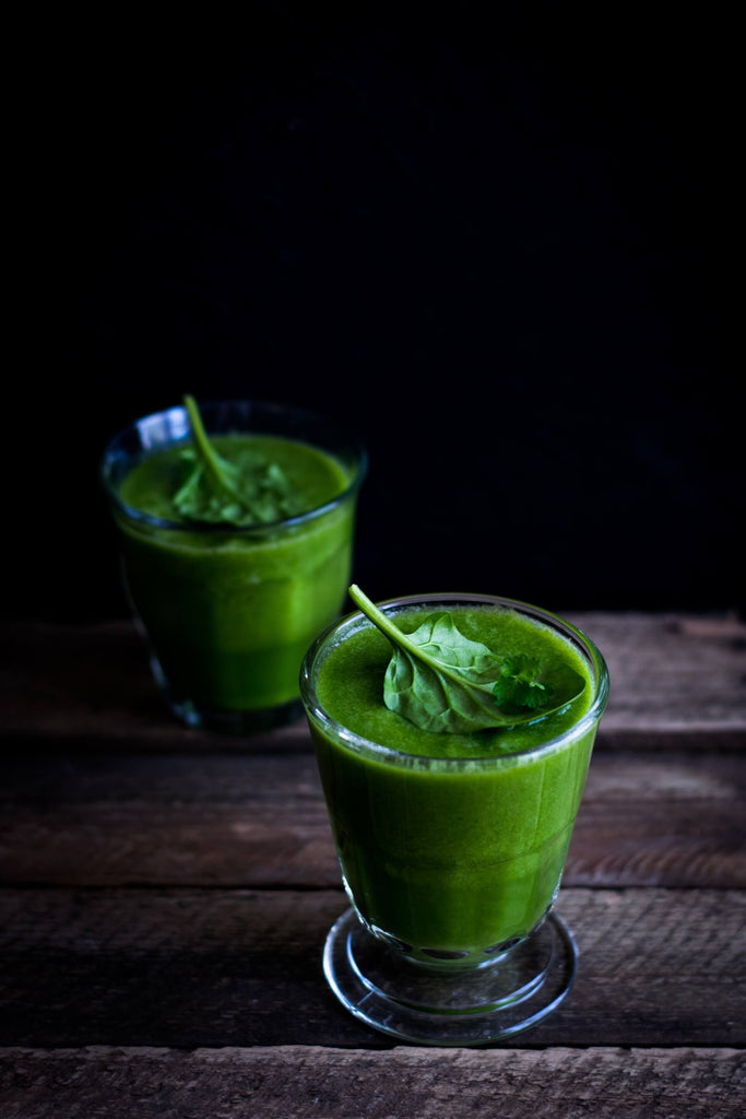 two glasses of green vegetable smoothies on wooden table