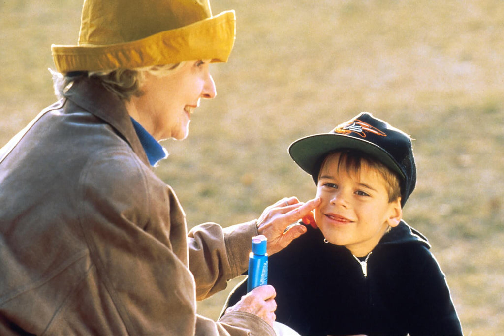 elderly woman holding skincare product applying it on a young boy's face