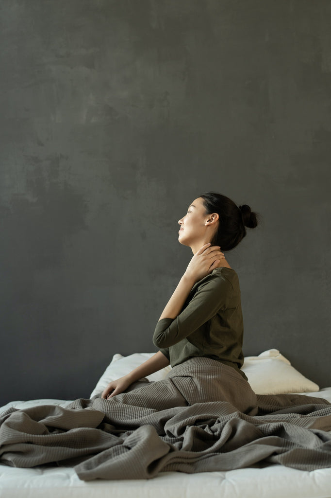 woman sitting on bed hand on her neck side view