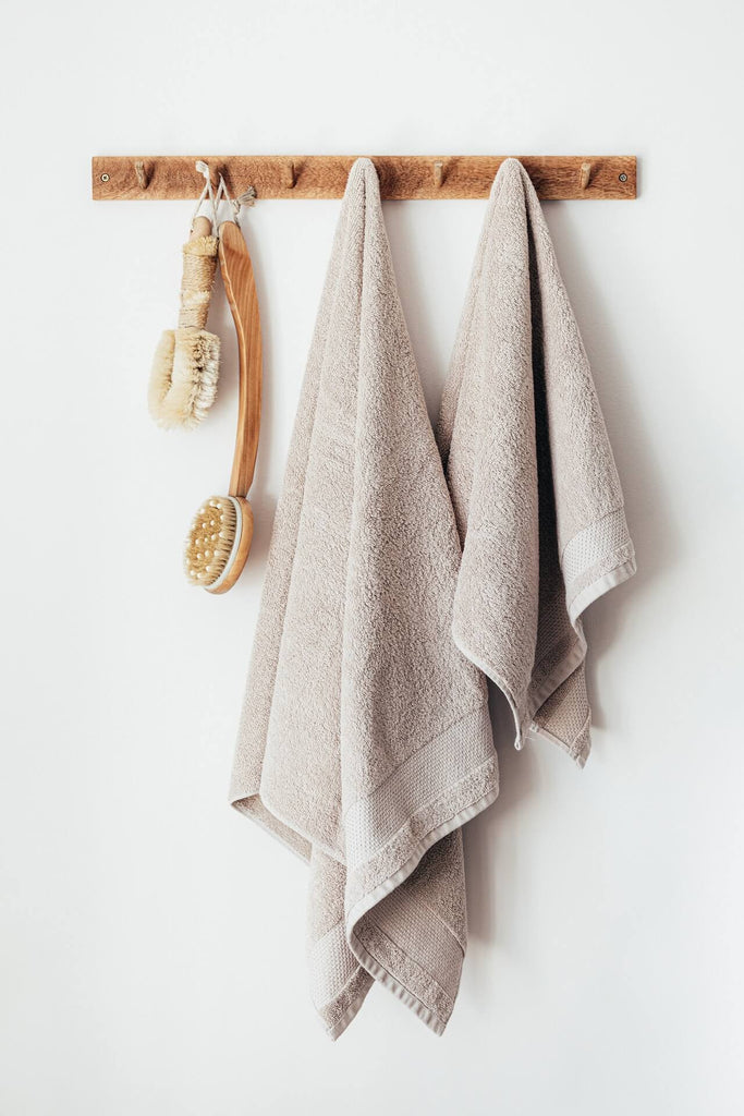 wood hangers hanging two bath towels and dry brushes