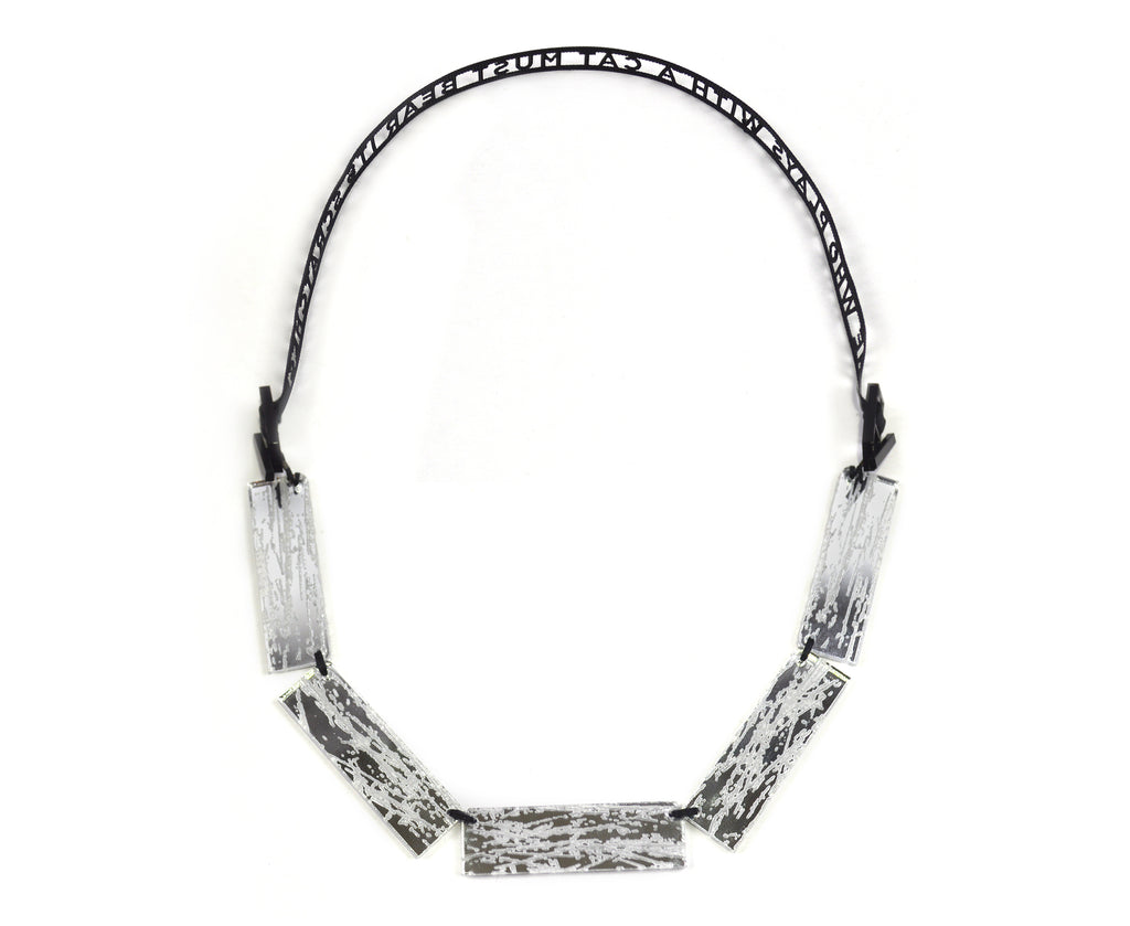 Laser Cut Ribbon Necklace: He who plays with a cat must bear its scratches.