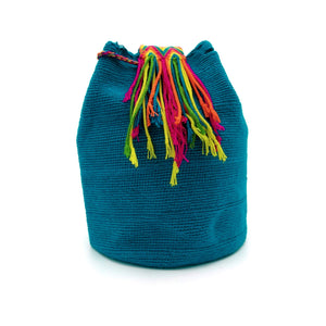 Side view of the Aquamarine Enchantment Wayuu Mochila Bag which has a vibrant array of the following colors: Cerulean (Dark-Aquamarine). Strap colors: Light-Green, Yellow, Bright-Orange-Red, Red, and Cerulean (Dark-Aquamarine)