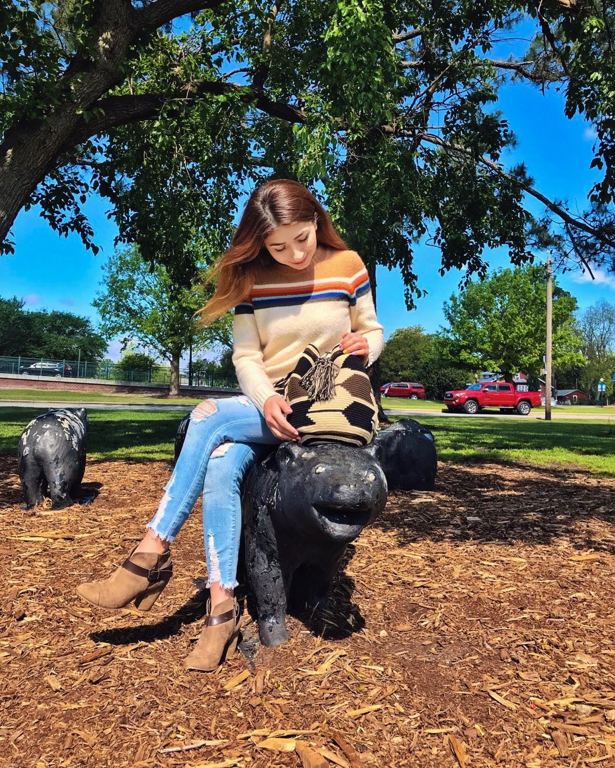 Young Woman Holds a beautiful Wayuu Mochila Bag with a pattern with arrows in colors Beige, Black, and Dark-Brown while sitting on a park bench.