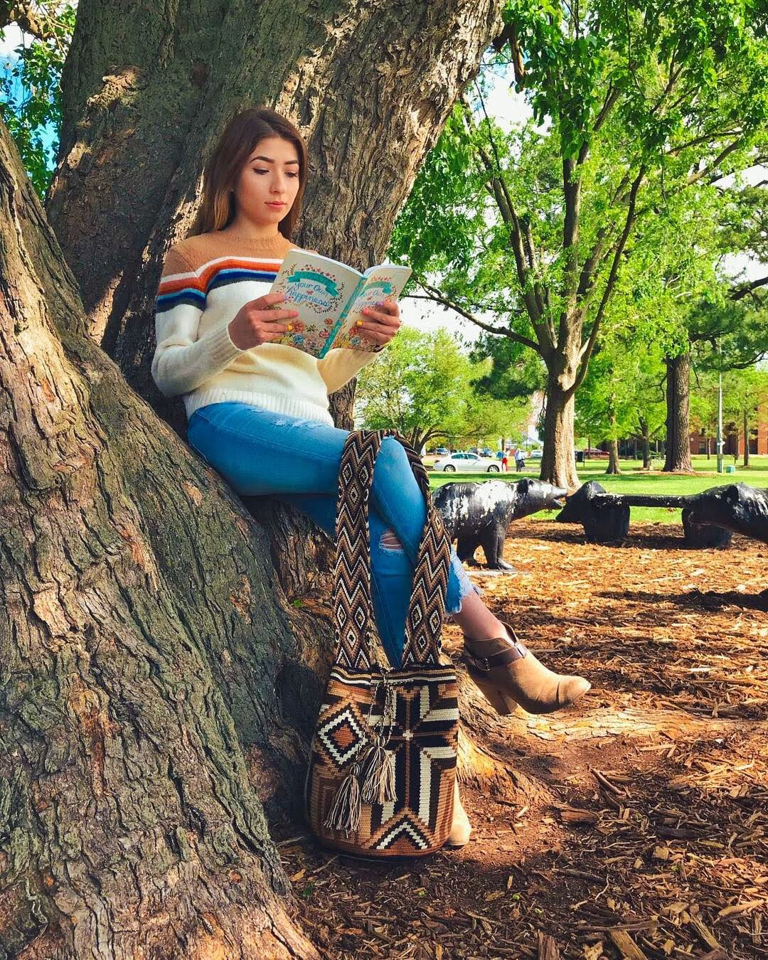 Young Woman Holds the Brown-Cross Wayuu Mochila Bag with a beautiful combination of the following colors: Beige, Light Brown, Brown, Dark Brown, and Black while reading sitting down on a tree.